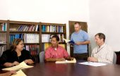 workers-seated-at-meeting-around-table-discussing-725x463